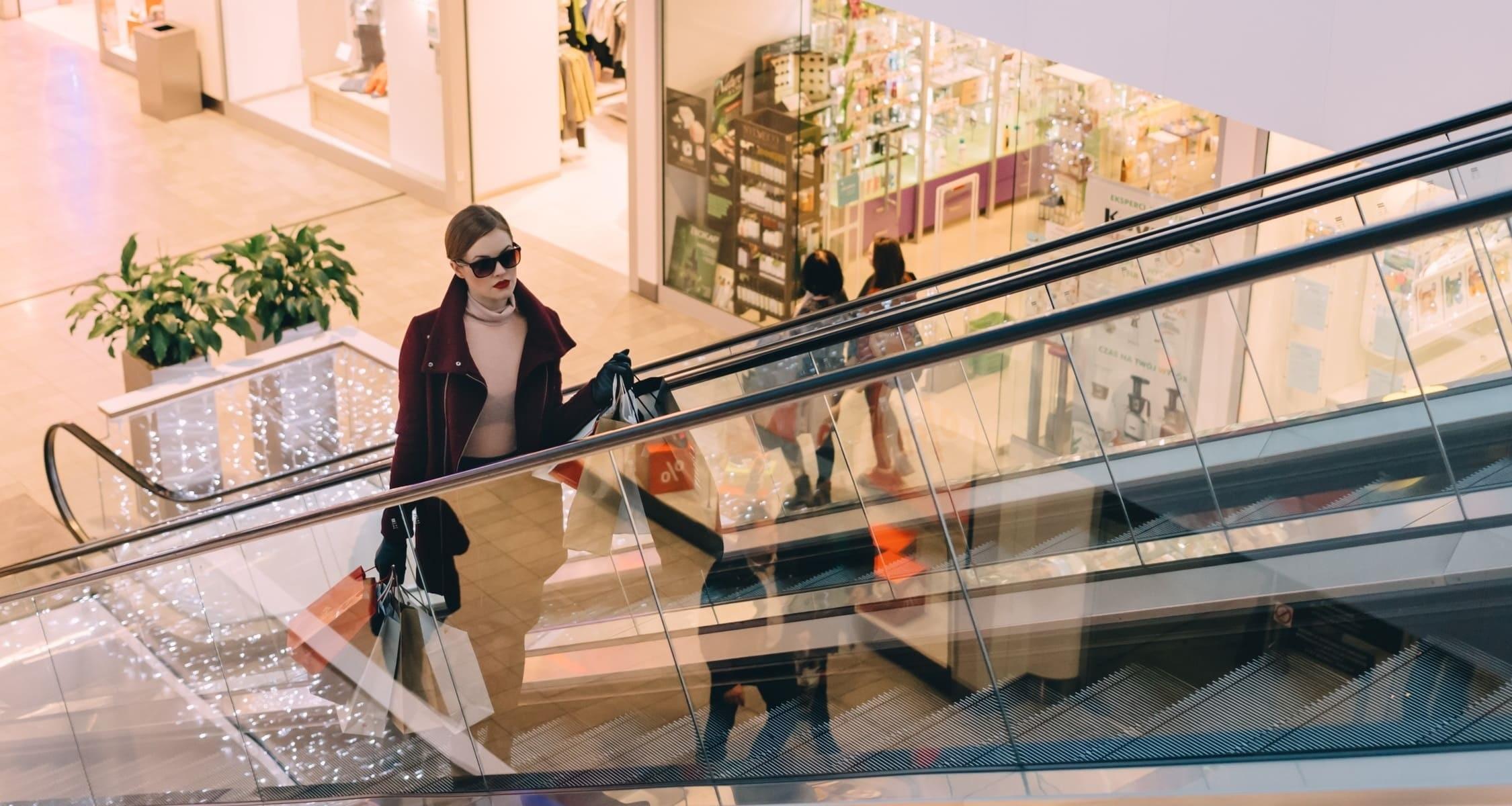 ragazza in un centro commerciale che sale le scale mobili